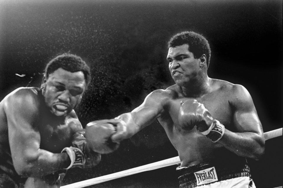 Photo - FILE - In this Oct. 1, 1975, file photo, spray flies from the head of challenger Joe Frazier as heavyweight champion Muhammad Ali connects with a right in the ninth round of their title fight in Manila, Philippines. Ali, the magnificent heavyweight champion whose fast fists and irrepressible personality transcended sports and captivated the world, has died according to a statement released by his family Friday, June 3, 2016. He was 74. (AP Photo/Mitsunori Chigita, File)
