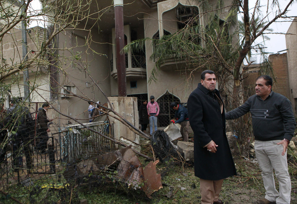 Photo - Civilians inspect their damaged house at the site of a car bombing in the Hurriyah neighborhood of northern Baghdad, Iraq, Monday, Feb. 3, 2014. Iraqi officials say car bombings on Monday in and near Baghdad have killed and wounded scores of people. (AP Photo/Hadi Mizban)