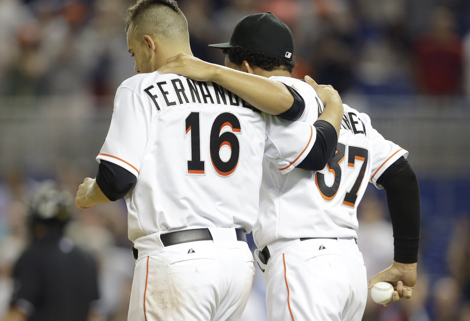 Photo - Miami Marlins starting pitcher Jose Fernandez (16) is congratulated by pitcher Henderson Alvarez (37) after a baseball game against the Atlanta Braves, Tuesday, April 29, 2014, in Miami. The Marlins defeated the Braves 9-0. (AP Photo)
