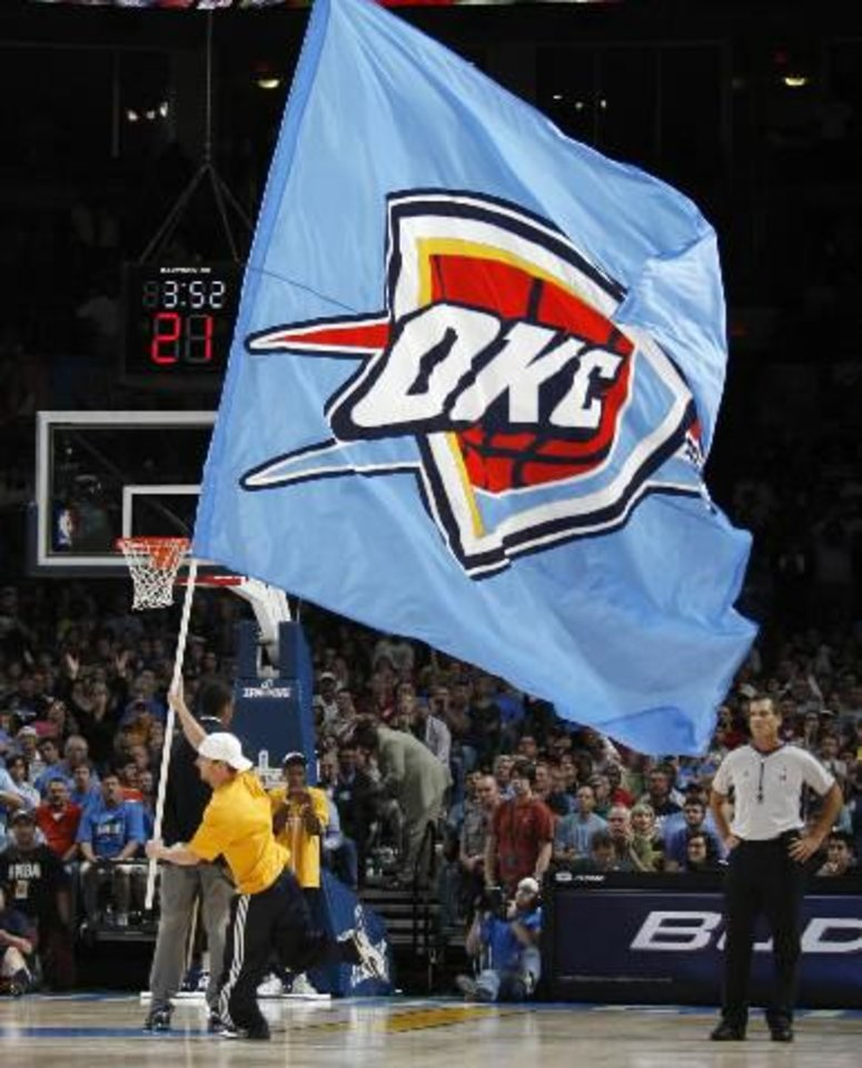 Photo - The  Oklahoma  City team  flag makes its way across the court in the fourth quarter during the NBA basketball game between the  Oklahoma  City  Thunder and the Minnesota Timberwolves at the Ford Center in  Oklahoma  City, Sunday, Nov. 2, 2008. The  Thunder won, 88-85. BY NATE BILLINGS, THE OKLAHOMAN