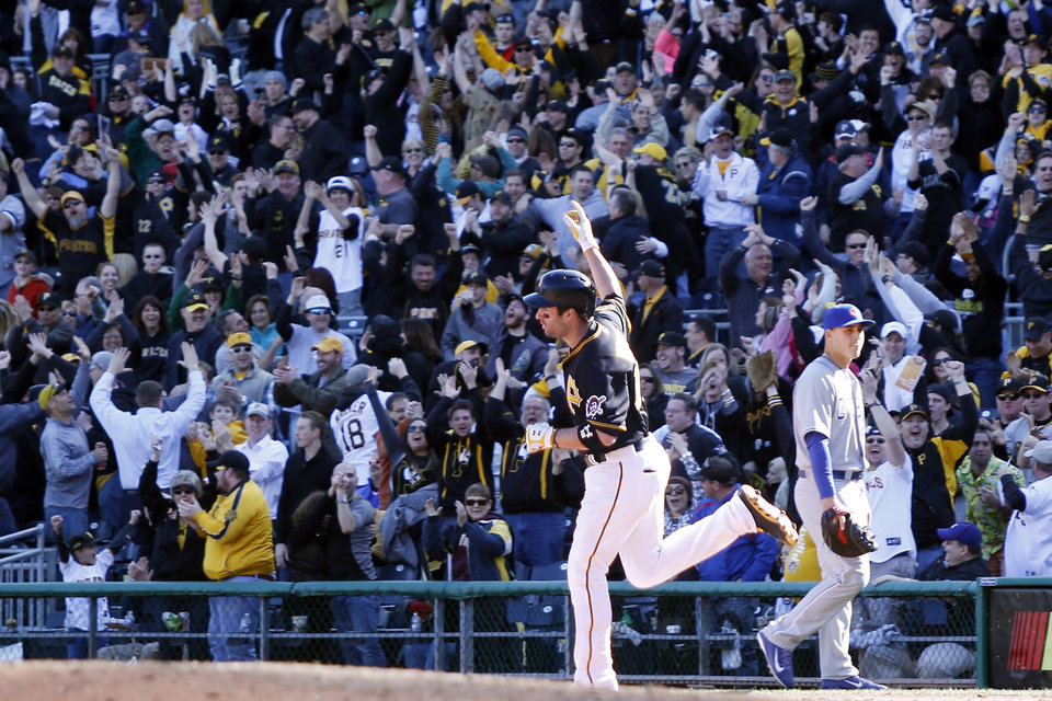 Photo - Fans cheer as Pittsburgh Pirates' Neil Walker (18) pumps his fist as he rounds the bases after hitting the game-winning home run while Chicago Cubs first baseman Anthony Rizzo, right, walks off the field in the tenth inning of an opening day baseball game against the Chicago Cubs on Monday, March 31, 2014, in Pittsburgh. The Pirates won 1-0 in ten innings. (AP Photo/Keith Srakocic)