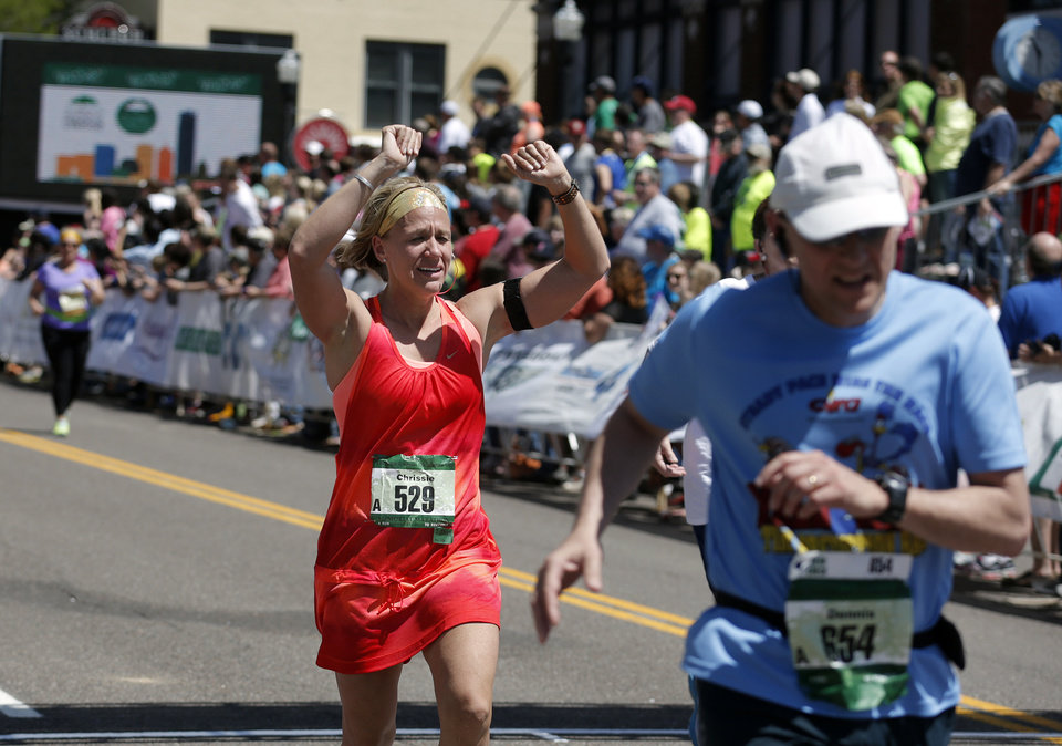 Chrissie Boatman of Tecumseh, Okla., cheers as she finishes the Marathon during the 14th Annual Oklahoma City Memorial Marathon in Oklahoma City, Sunday, April 27, 2014. Photo by Sarah Phipps, The Oklahoman