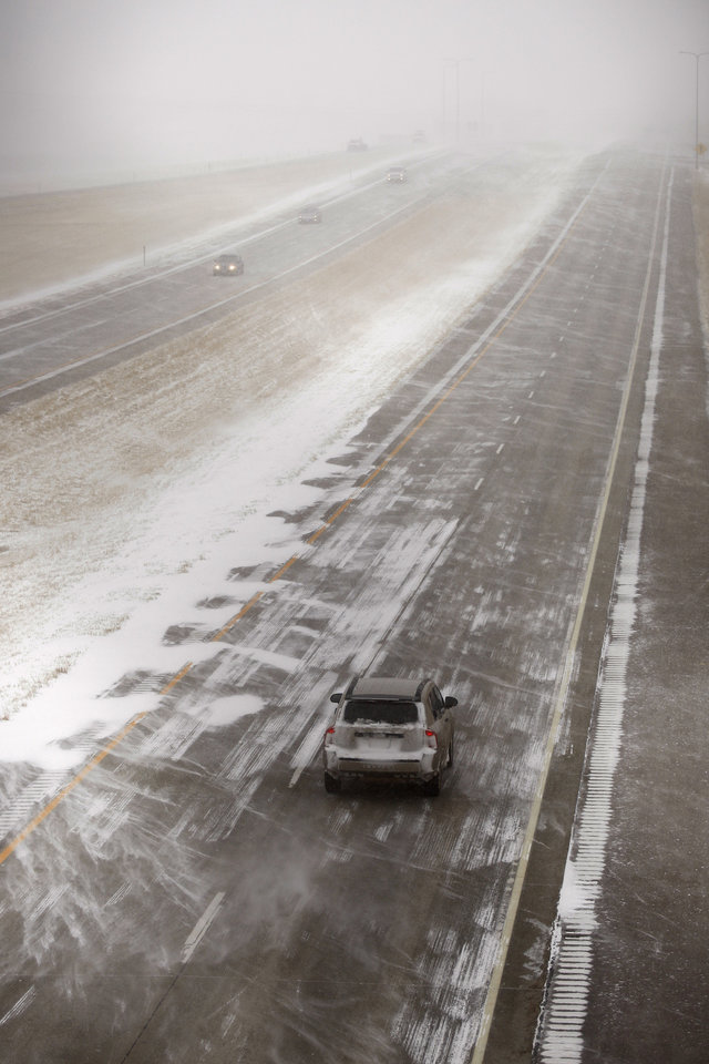 Photo - Cars drive along Interstate 90 near Black Hawk as a spring storm blasts the Black Hills in South Dakota on Monday, March 31, 2014.  A spring snowstorm in the Upper Midwest on Monday shut down public schools, universities and government offices, made travel hazardous and life miserable for cattle ranchers in the midst of calving season. The National Weather Service issued blizzard warnings for much of the Dakotas and part of Minnesota, with the heaviest snow expected in eastern North Dakota and northwestern Minnesota.  (AP Photo/Rapid City Journal, Benjamin Brayfield)