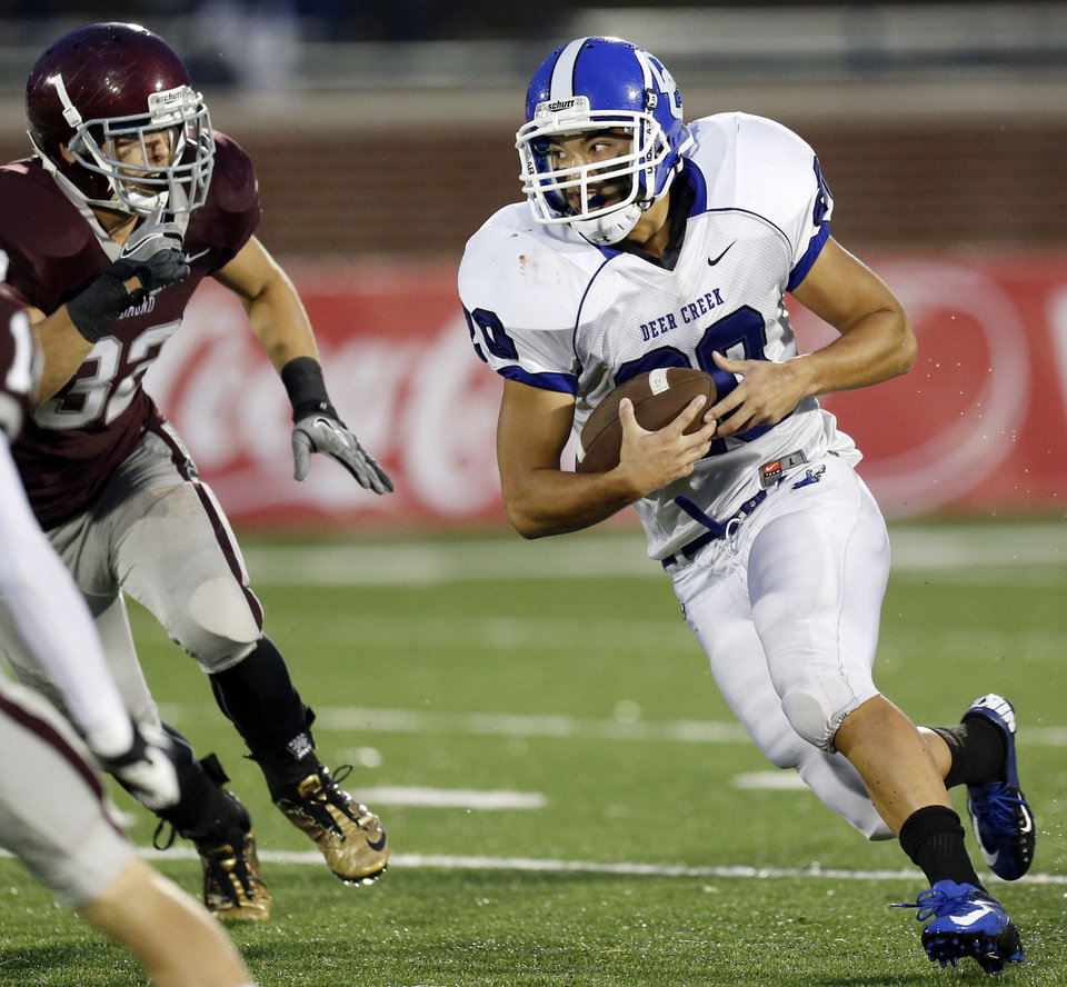 Photo - Deer Creek's Brennan Miyake (20) tries to get past Edmond Memorial's Jason Hand (32) on a carry during a high school football game between Edmond Memorial and Deer Creek at Wantland Stadium in Edmond, Okla., Thursday, Sept. 13, 2012. Photo by Nate Billings, The Oklahoman