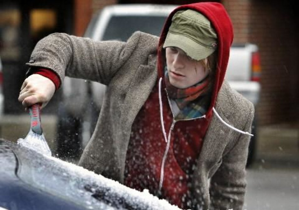 Photo - Joseph Rosser of Oklahoma City clears his car windows of ice as a winter storm moves into the area on Thursday, Jan. 28, 2010, in Norman, Okla. Photo by Steve Sisney