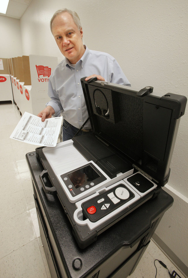 Photo - Oklahoma County Election Board Secretary Doug Sanderson displays a sample ballot and one of the new vote-counting devices. Oklahomans will have the chance to try the system this week at county election board offices across the state. PHOTO BY PAUL B. SOUTHERLAND, THE OKLAHOMAN