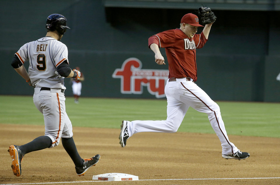 Photo - Arizona Diamondbacks' Trevor Cahill, right, jumps off of first base after getting San Francisco Giants' Brandon Belt (9) out during the first inning of a baseball game, Wednesday, April 2, 2014, in Phoenix. (AP Photo/Ross D. Franklin)