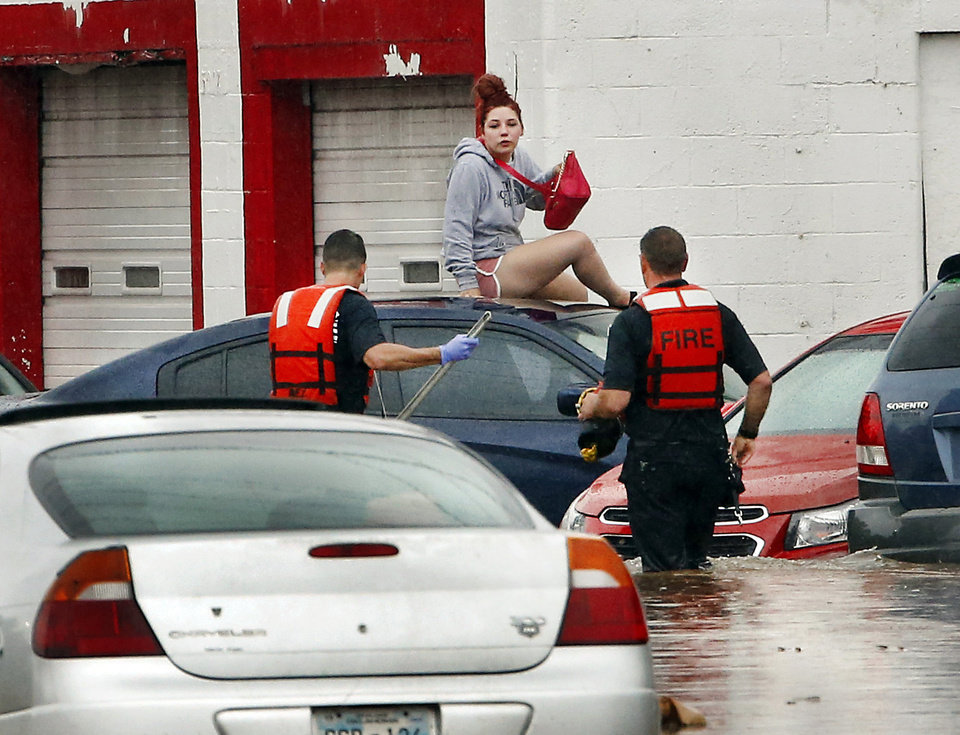 Photo - Oklahoma City firefighters rescue a woman who climbed to the roof of her car as waters on S. May Avenue rose during heavy rain Thursday morning, June 6, 2019.  Firefighters said they assisted four people to safety between 11 o'clock and noon in the deep water that flooded the intersection of SW 29 and May.  [Jim Beckel/The Oklahoman]