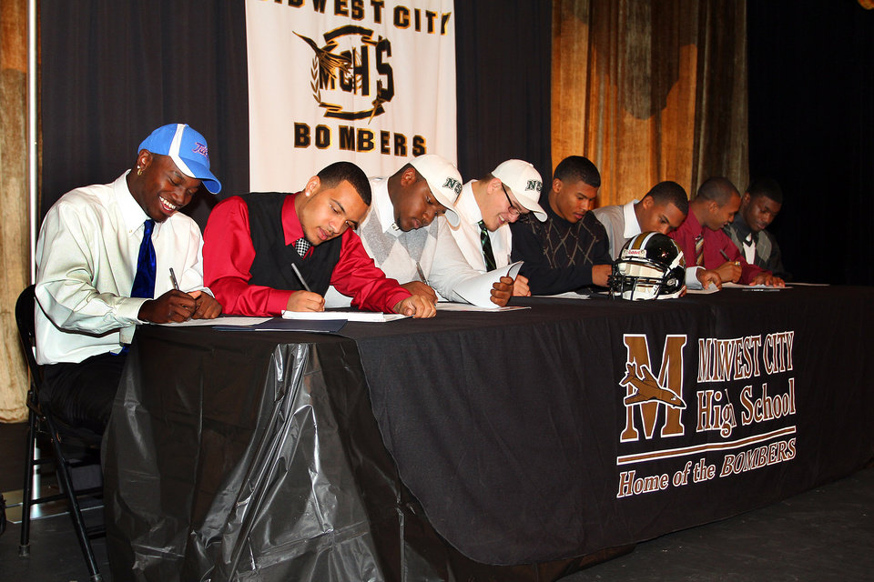 Photo - Eight Midwest City High School football players signed letters of intent at Midwest City High School Tuesday, February 1, 2012. Left to right, James Flanders signed with The University of Tulsa, Zeke Lewis with The University of South Dakota, Devin Crisp with Northeastern Oklahoma State, Dakota Moran with Northeastern Oklahoma State, Ronnie Davis with Northeastern Oklahoma State, Rickey Reeves with the University of South Dakota, Myles Hogg with Southern Nazarene University and CJ Smith with Emporia State University. PHOTO BY HUGH SCOTT, FOR THE OKLAHOMAN  ORG XMIT: KOD