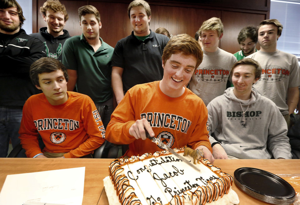 Photo - With his teammates around him, Jacob Lewis slices the cake after signing his letter. Irish senior quarterback  Jacob Lewis signed a letter of intent to play at Princeton during a signing day ceremony at Bishop McGuinness High School on Wednesday, Feb. 5, 2014.    Photo by Jim Beckel, The Oklahoman