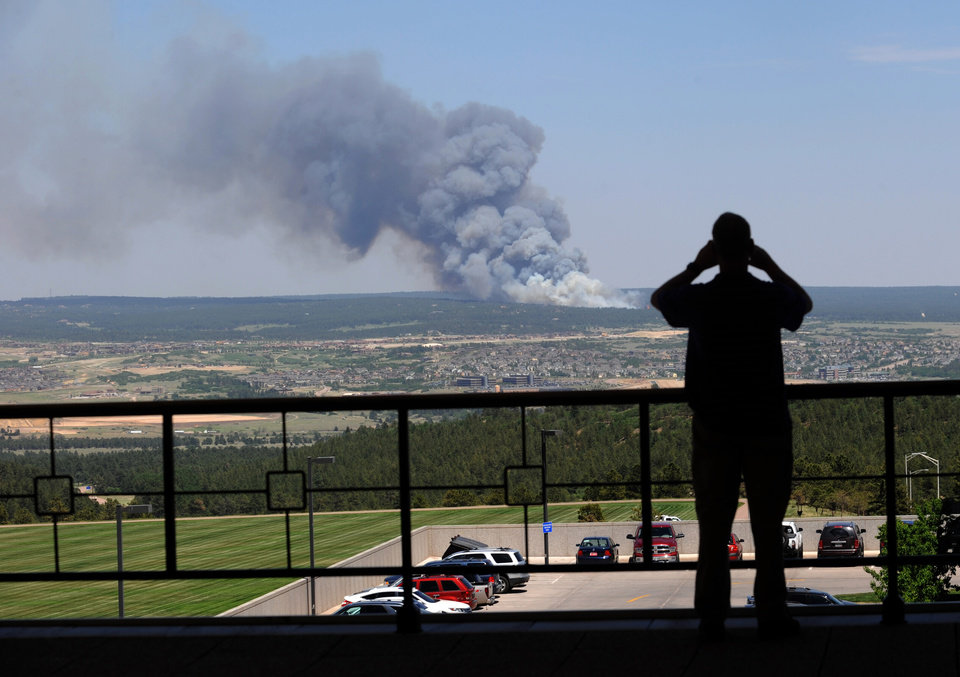 Photo - A man watches as a fire byrns out of control north of Shoupe Road and East of Highway 83 in Colorado Springs, Colo. on Tuesday afternoon, June 11, 2013.  The Black Forest Fire was one of at least three significant wildfires burning in Colorado amid gusty winds and record-breaking hot, dry weather. (AP Photo/The Colorado Springs Gazette, Christian Murdock) MAGS OUT