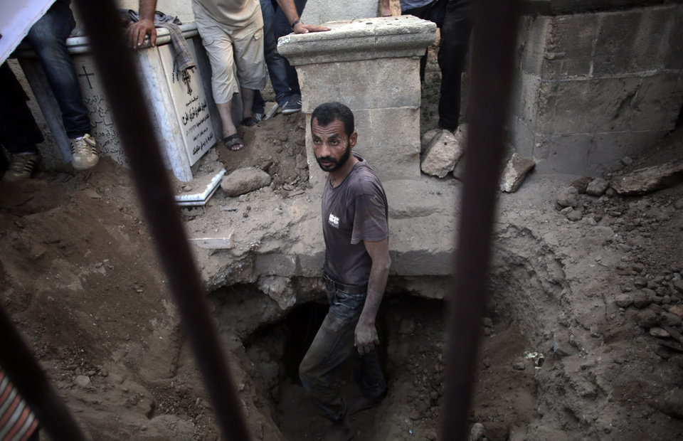 Photo - Mourners bury the body of Christian woman Jalila Ayyad, 70, who was killed in an Israeli strike that destroyed her house, during her funeral in Gaza City on Sunday, July 27, 2014. (AP Photo/Khalil Hamra)