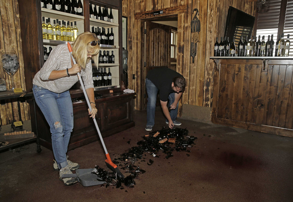 Photo - Janelle Dahl and her son Austin clean up broken bottles of wine in a tasting room after an earthquake at Dahl Vineyards Sunday, Aug. 24, 2014, in Yountville, Calif. A large earthquake rolled through California's northern Bay Area early Sunday, damaging some buildings, igniting fires, knocking out power to tens of thousands and sending residents running out of their homes in the darkness. (AP Photo/Eric Risberg)