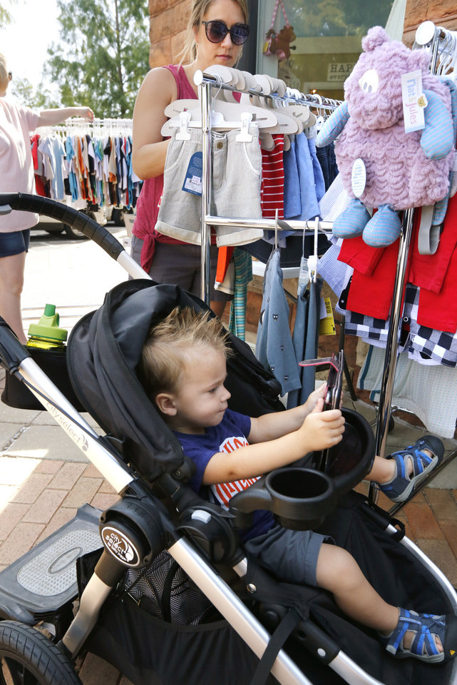 Photo -  Jax Ault stays busy on a tablet while his mother, Lindsey, shops for his clothes. [PHOTO BY PAUL HELLSTERN, THE OKLAHOMAN]