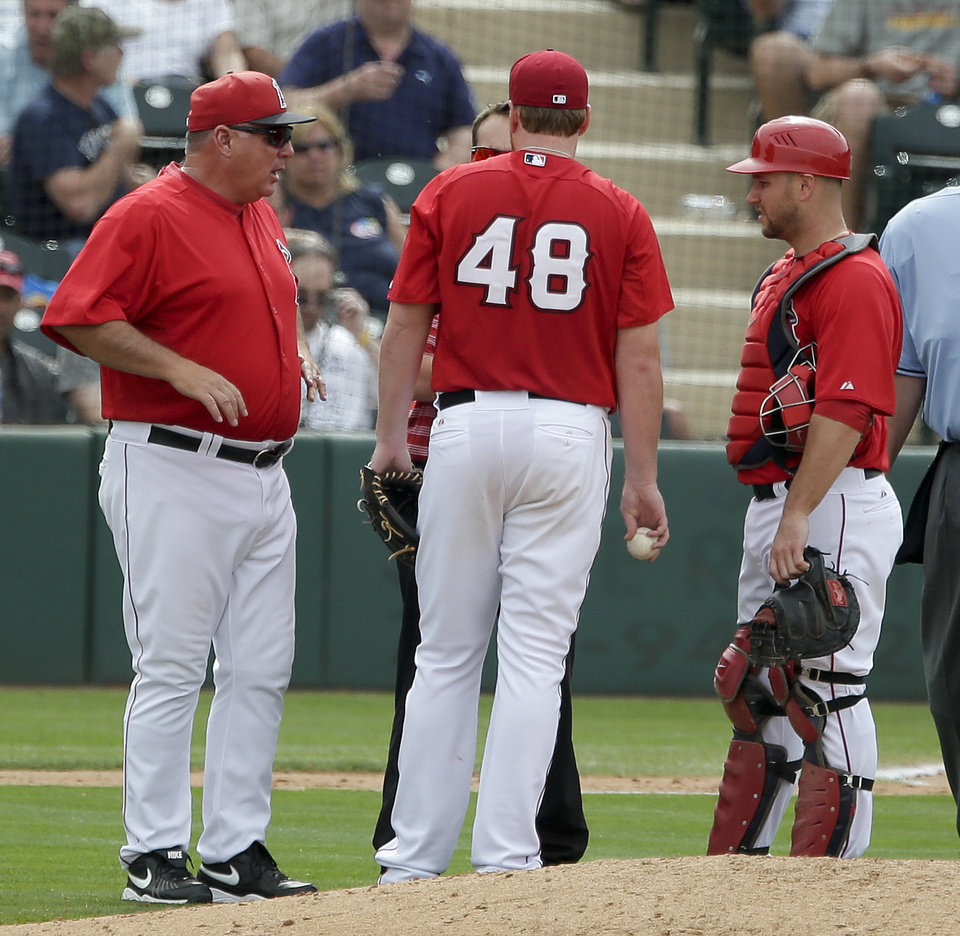 Los Angeles Angels manager Mike Scioscia, left, talks to a trainer after starting pitcher Tommy Hanson, center, was hurt in the fourth inning as catcher Chris Iannetta looks on during spring training baseball game against the Cleveland Indians in Tempe, Ariz.,Wednesday, March 20, 2013. (AP Photo/Chris Carlson)