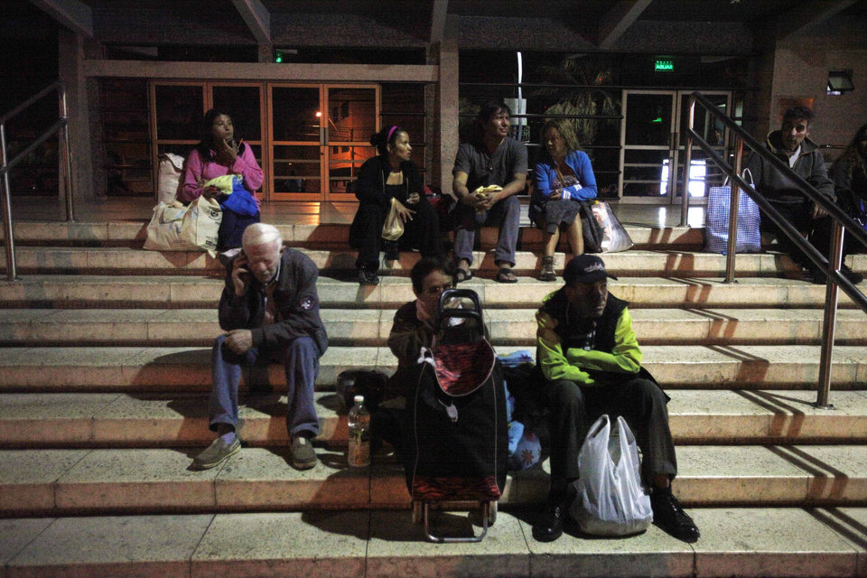 Photo - People sit outside a hospital after a strong aftershock in Arica, Chile, early Thursday, April 3, 2014. A powerful 7.8-magnitude aftershock hit Chile's far-northern coast late Wednesday night, shaking the same area where a magnitude-8.2 earthquake hit just a day before causing some damage and six deaths. (AP Photo/Luis Hidalgo)