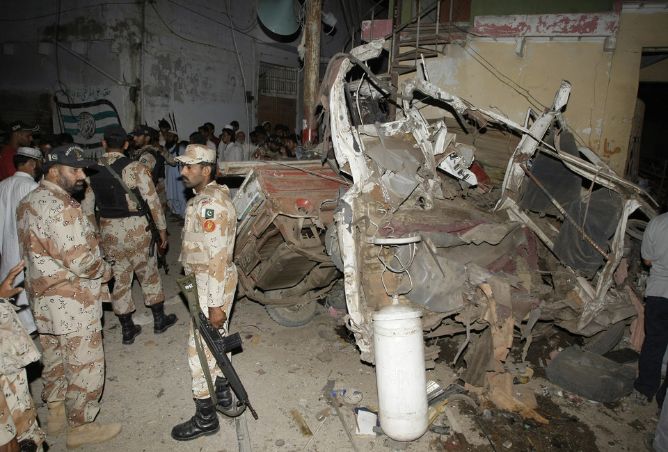 Photo - Pakistani para-military troops cordon off the site of an explosion in Karachi, Pakistan Friday, April 26, 2013.  A bomb planted near the office of a political party threatened by the Taliban has killed many people in southern Pakistan, police said. (AP Photo/Fareed Khan)