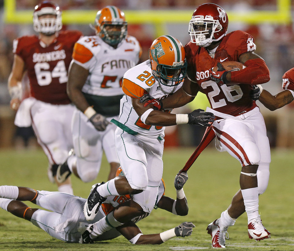 Oklahoma\'s Damien Williams (26) fights off Florida A&M\'s Johnathan Butler (28), and Antwain Mathews (16) during the college football game between the University of Oklahoma Sooners (OU) and Florida A&M Rattlers at Gaylord Family—Oklahoma Memorial Stadium in Norman, Okla., Saturday, Sept. 8, 2012. Photo by Bryan Terry, The Oklahoman