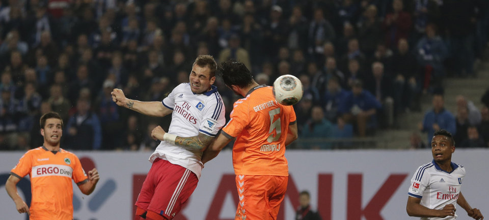 Photo - Hamburg's Pierre-Michel Lasogga, left, and Fuerth's Mergim Mavraj challenge for the ball during their 1st leg relegation soccer match between Hamburger SV and Greuther Fuerth in Hamburg, Germany, Thursday, May 15, 2014.  (AP Photo/Matthias Schrader)
