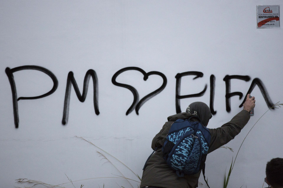 Photo - A masked protester writes