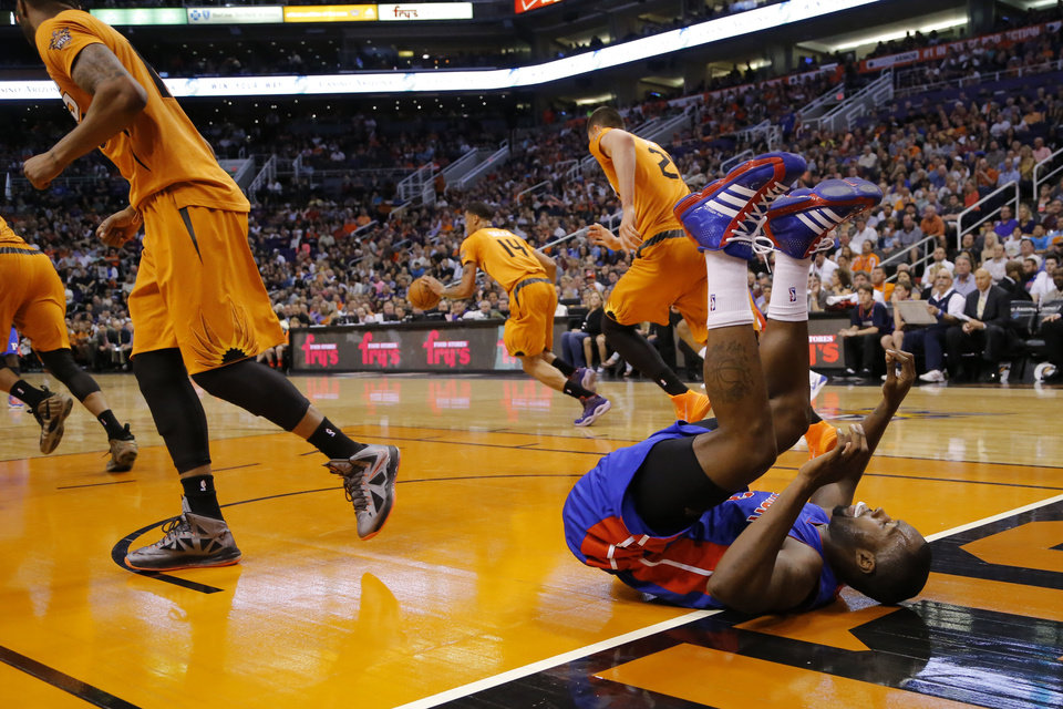 Photo - Detroit Pistons' Rodney Stuckey, right, falls after shooting as the Phoenix Suns push the ball up court during the first half of an NBA basketball game, Friday, March 21, 2014, in Phoenix. (AP Photo/Matt York)