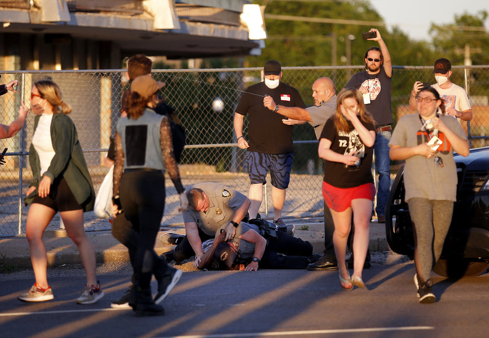 Photo - Protesters run from mace as Oklahoma City Police arrest a man during a protest near the intersection of 23rd and Classen in Oklahoma City, Saturday, May 30, 2020. The protest was in response to the death of George Floyd. [Sarah Phipps/The Oklahoman]