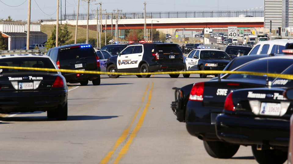 Photo - Norman police vehicles block the I-35 west access road in front of Nextep at the scene of a hostage situation in Norman Monday, Nov. 10, 2014.  Photo by Paul B. Southerland, The Oklahoman