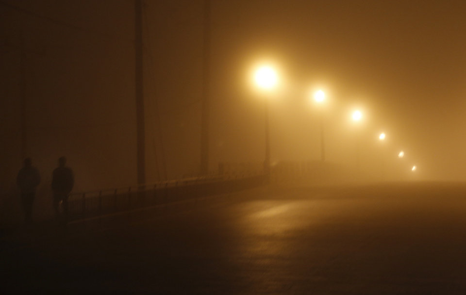 People walk across the Walnut Street bridge in dense fog in Oklahoma City, Sunday, Dec. 1, 2013. Photo by Sarah Phipps, The Oklahoman