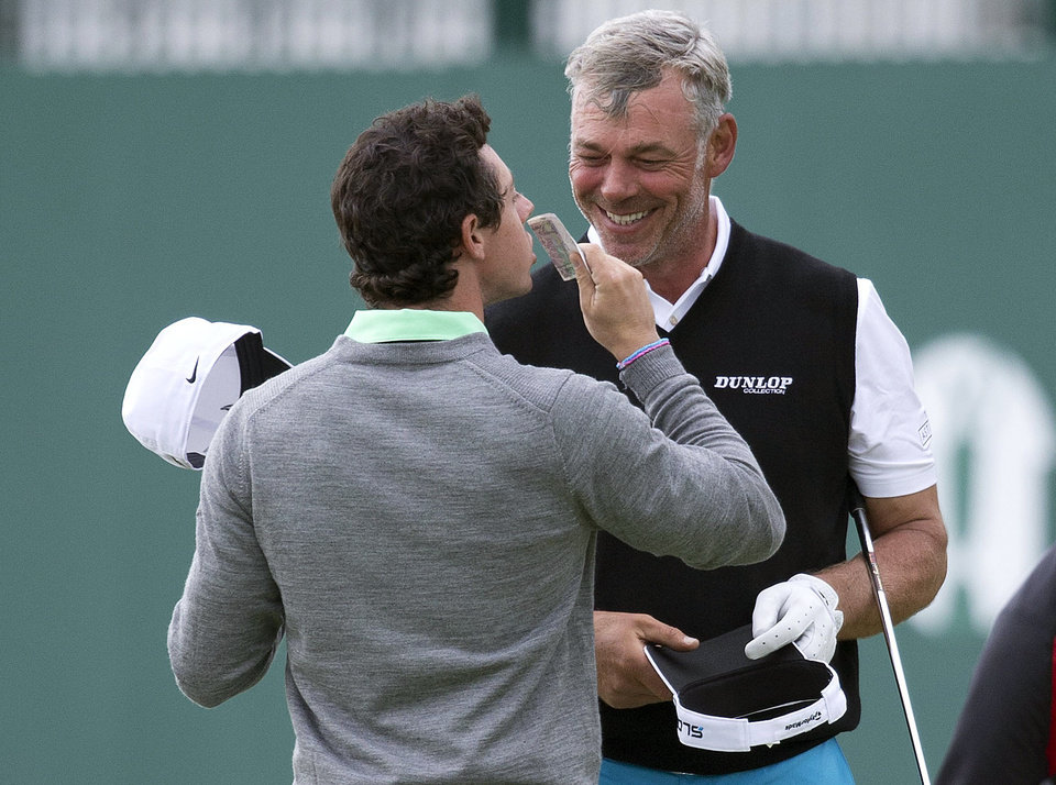 Photo - Rory McIlroy, of Northern Ireland, kisses a 20 pound note as Darren Clarke, of Northern Ireland, smiles after winning a wager on the 18th green after holing a putt during a practice round for the British Open Golf championship at the Royal Liverpool golf club, Hoylake, England, Wednesday, July 16, 2014. The British Open Golf championship starts Thursday, July 17. (AP Photo)