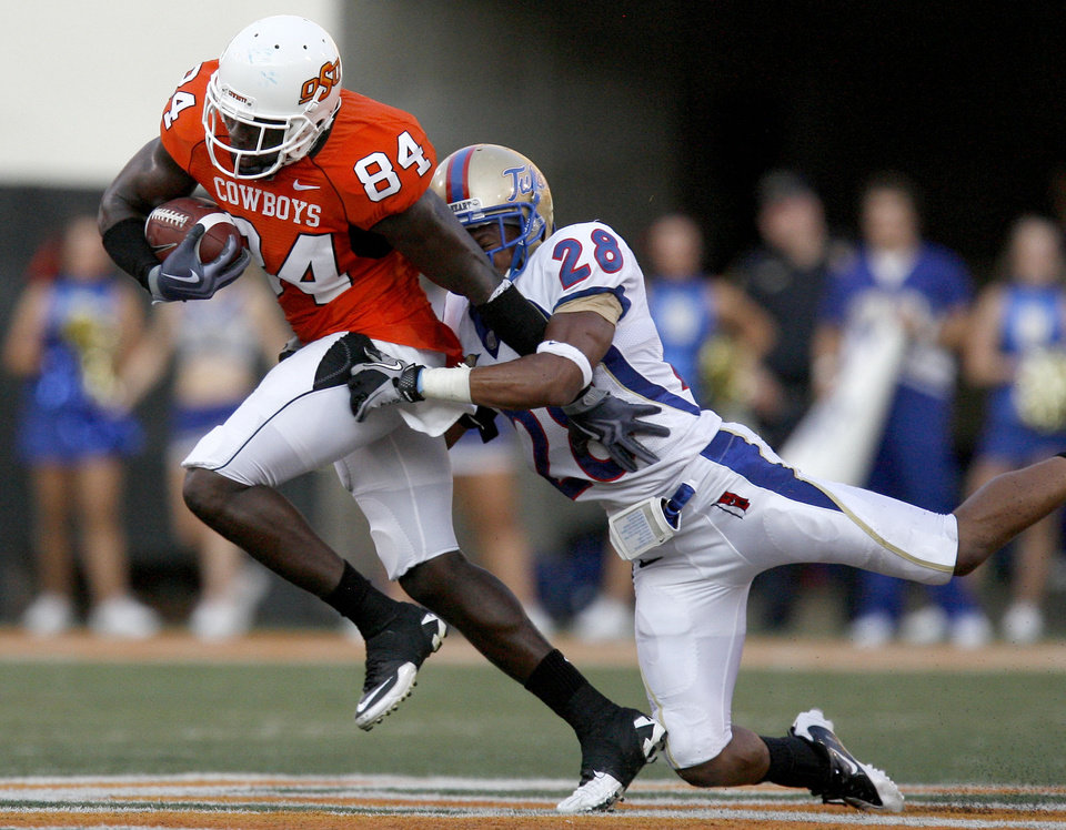 Oklahoma State wide receiver Hubert Anyiam (84) tries to shake loose Tulsa's Lowell Rose (28) during the college football game between the University of Tulsa (TU) and Oklahoma State University (OSU) at Boone Pickens Stadium in Stillwater, Oklahoma, Saturday, September 18, 2010. Photo by Sarah Phipps, The Oklahoman
