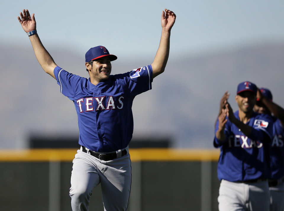 Photo - Texas Rangers' Martin Perez leads a line of pitchers in stretching before a morning workout during spring training baseball practice, Monday, Feb. 17, 2014, in Surprise, Ariz. (AP Photo/Tony Gutierrez)