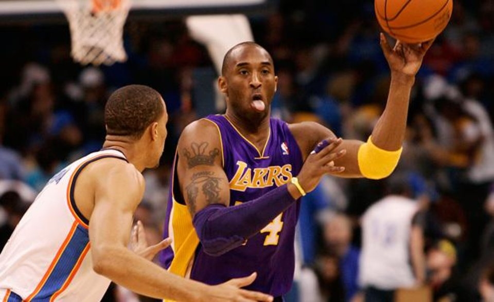 Photo - Los Angeles Lakers guard Kobe Bryant passes the ball around Oklahoma City Thunder guard Thabo Sefolosha, of Switzerland, during the first half of an NBA basketball game Sunday, Feb. 27, 2011, in Oklahoma City. (AP Photo/James Schammerhorn)