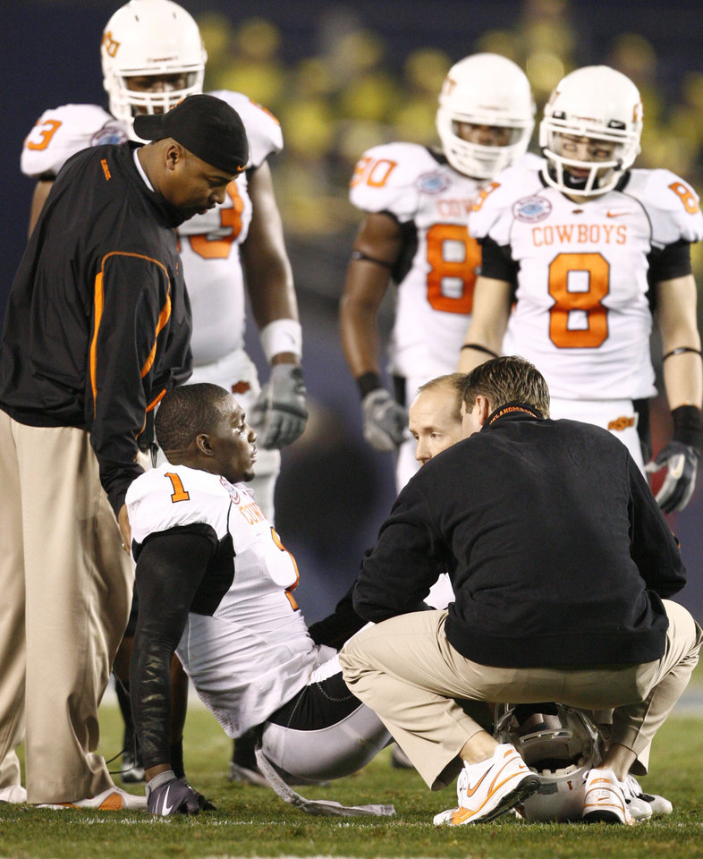 Photo - OSU's Dez Bryant sits on the field after an injury during the Holiday Bowl college football between Oklahoma State and Oregon at Qualcomm Stadium in San Diego, Tuesday, Dec. 30, 2008.  PHOTO BY BRYAN TERRY, THE OKLAHOMAN.
