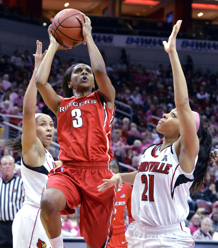 Photo - Rutgers' Tyler Scaife, center puts up a shot between the defense of Louisville's Tia Gibbs, left, and Bria Smith during the first half of an NCAA college basketball game, Sunday, Feb. 23, 2014, in Louisville, Ky. (AP Photo/Timothy D. Easley)