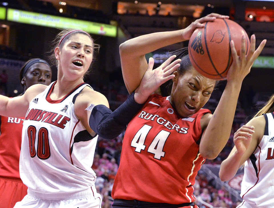 Photo - Louisville's Sara Hammond, left, attempts to grab a rebound away from Rutgers' Betnijah Laney during the first half of an NCAA college basketball game, Sunday, Feb. 23, 2014, in Louisville, Ky. (AP Photo/Timothy D. Easley)