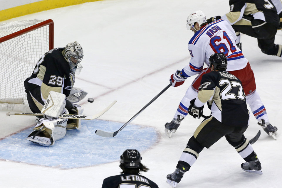 Photo - Pittsburgh Penguins goalie Marc-Andre Fleury (29) stops a shot by New York Rangers' Rick Nash (61) in the first period of game 2 of a second-round NHL playoff hockey series in Pittsburgh Sunday, May 4, 2014. (AP Photo/Gene J. Puskar)