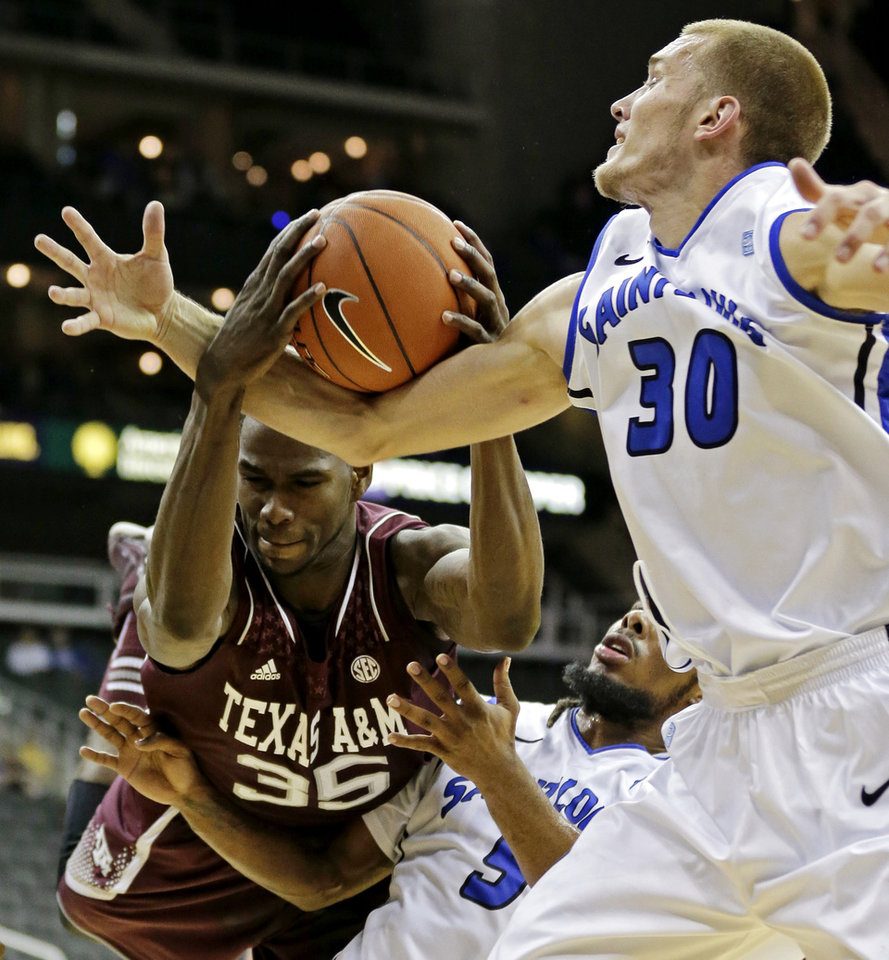Photo -   Texas A&M forward Ray Turner (35) battles Saint Louis forward Jake Barnett (30) and guard Jordair Jett (5) for a rebound during the first half of an NCAA college basketball game, Monday, Nov. 19, 2012, in Kansas City, Mo. (AP Photo/Charlie Riedel)
