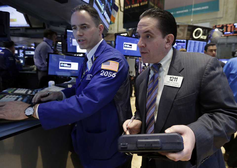 Photo - Specialist Jason Hardzewicz works with trader Tommy Kalikas on the floor of the New York Stock Exchange, Tuesday, April 22, 2014. Stock futures edged higher as more companies reported first quarter earnings. (AP Photo/Richard Drew)