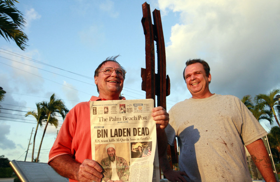 Photo - Lee White, left,  and Richard Nightingale, smile while holding a newspaper featuring the story of the death of Osama Bin Laden, at a memorial for people killed in the Sept. 11, 2001 attacks,  in Palm Beach Gardens, Fla., Monday May 2, 2011.  Osama bin Laden, the face of global terrorism and architect of the Sept. 11, 2001, attacks, was killed in a firefight with elite American forces in Pakistan on Monday, then quickly buried at sea in a stunning finale to a furtive decade on the run. (AP Photo/The Palm Beach Post, Lannis Waters) ** MAGS OUT. TV OUT. NO SALES ** ORG XMIT: FLPAP102