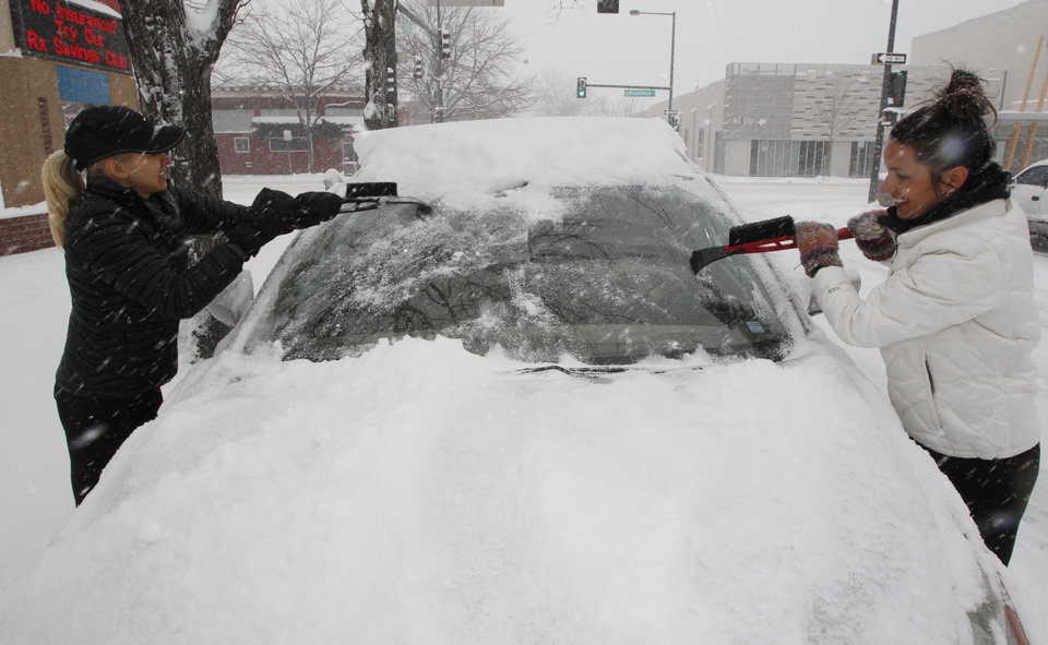 Working in tandem in downtown Denver, Carie Mueller, left, cleans the windshield of a four-wheel-drive vehicle with its owner, Kristy Teigen, both of Denver, as a spring storm packing high winds and heavy snow sweeps over Colorado's Front Range and on to the eastern plains on Saturday, March 23, 2013. Forecasters predict up to a foot of snow will fall in some locations in Colorado before the storm heads toward the nation's midsection. (AP Photo/David Zalubowski)