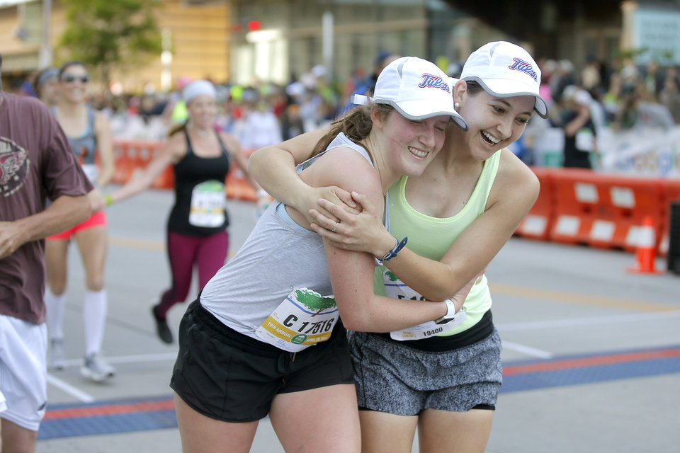 Photo - Audrey Wise, left, and Lauren Milburn celebrate after running the half marathon during the Oklahoma City Memorial Marathon in Oklahoma City, Sunday, April 28, 2019. [Bryan Terry/The Oklahoman]