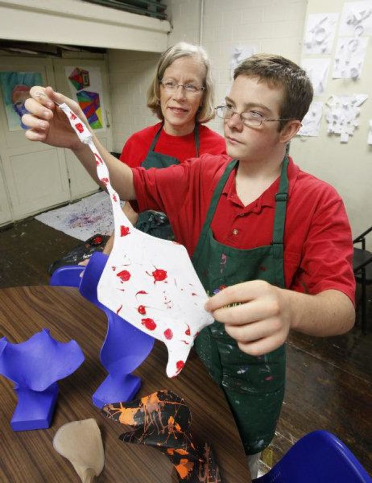 Photo - Barbara Williams, a volunteer from Mayflower United Church of Christ, looks at a sculpture being painted by seventh-grader Dylan Buck, 14 , during the