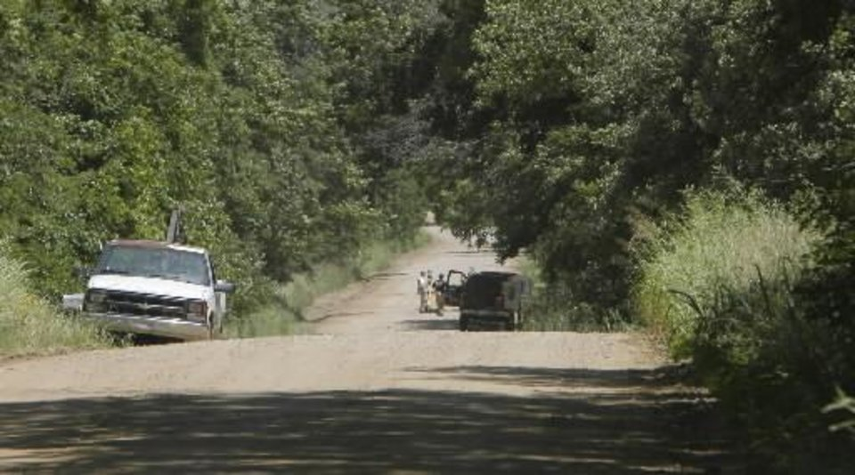 Photo - OSBI investigators closed the road past the crime scene to look for more clues in the deaths of Taylor Paschal-Placker and Skyla Whitaker who were shot and killed last Sunday on the dirt road near one of their homes, Thursday, June 12, 2008. The white truck is parked at the driveway of the Placker home and the man in the road is at the crime scene. Photo by David McDaniel