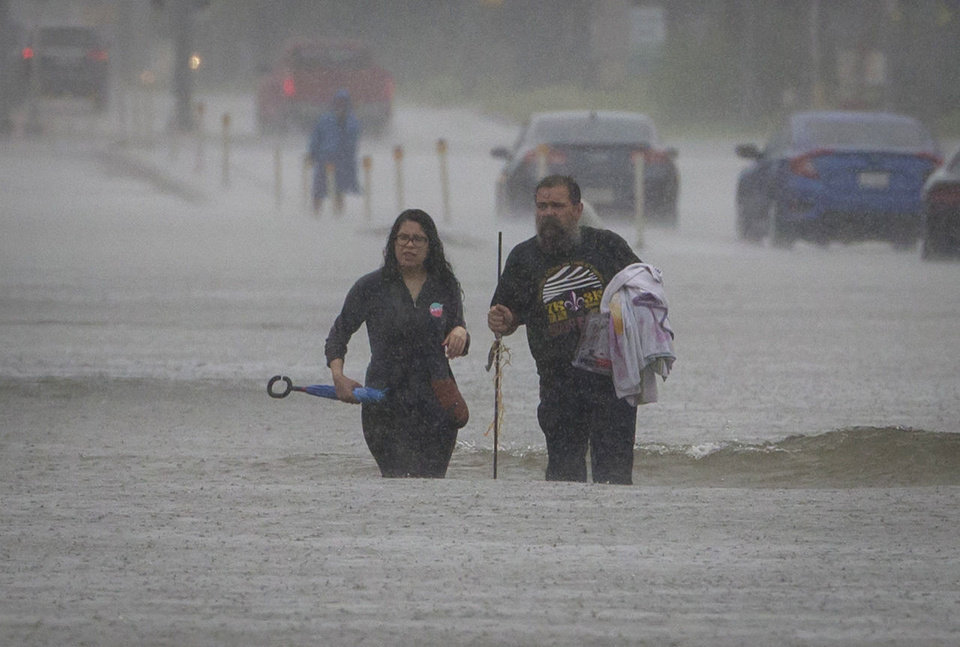 Photo - People carry their belongings through flooded section of FM 518 near the intersection with Interstate 45 in League City, Texas, as rain from Tropical Storm Harvey continues to fall Sunday, Aug. 27, 2017. (Stuart Villanueva/The Galveston County Daily News via AP)