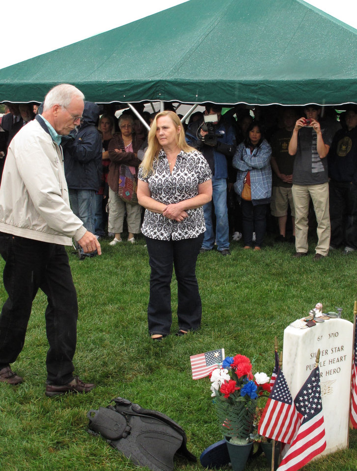 In this Oct. 2, 2012 photo, Daniel, left, and Maureen Murphy, the parents Navy SEAL Lt. Michael Murphy attend a memorial service at the gravesite for their son at at Calverton National Cemetery in Calverton, N.Y. The memorial service was attended by crew from the USS Michael Murphy, a Navy destroyer named for the Medal of Honor recipient killed in Afghanistan in 2005. The ship will be commissioned at a ceremony in New York City on Saturday, Oct. 6, 2012. (AP Photo/Frank Eltman)