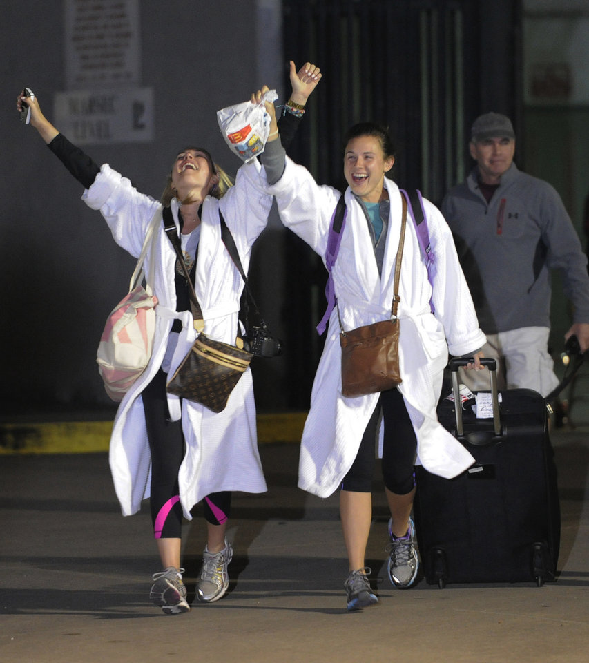 Photo - Kendall Jenkins, left, of Houston, celebrates with Brittany Ferguson, of Houston, after getting off the Carnival Triump in Mobile, Ala., Thursday, Feb. 14, 2013. The ship with more than 4,200 passengers and crew members has been idled for nearly a week in the Gulf of Mexico following an engine room fire. (AP Photo/John David Mercer)