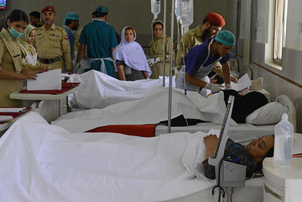 Photo - Pakistani army doctors attend victims of a suicide attack, at a military hospital in Quetta, Pakistan, Monday, June 9, 2014. Four suicide bombers targeted Shiite pilgrims staying at a hotel in the town of Tuftan near the Iranian border, said Baluchistan province Home Minister Mir Sarfraz Bugti. One bomber was killed by security officials traveling with the pilgrims, but the other three managed to get inside the hotel where they blew themselves up in an attack that also wounded many people, he said. (AP Photo/Arshad Butt)