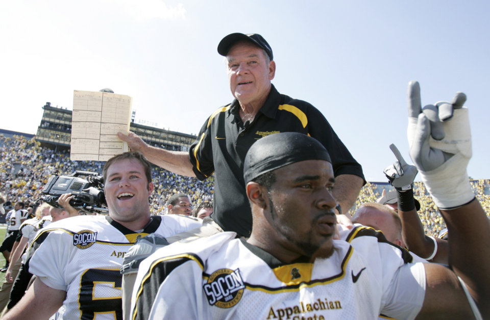 Photo - Appalachian State University coach Jerry Moore is carried off the field at Michigan Stadium by players Tony Robertson, right, and Brad Coley, left, after upsetting No. 5 University of Michigan 34-32 in a college football game Saturday, Sept. 1, 2007 in Ann Arbor, Mich. (AP Photo/Duane Burleson) ORG XMIT: AAS106