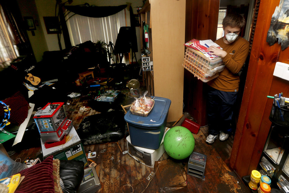 Photo - Andrew Seemar, 13, removes items from a room as he and his mother Kathleen Seemar clean up after their home was flooded during superstorm Sandy, Thursday, Nov. 1, 2012, in Brick, N.J. Three days after Sandy slammed the mid-Atlantic and the Northeast, New York and New Jersey struggled to get back on their feet, the U.S. death toll climbed to more than 80, and more than 4.6 million homes and businesses were still without power. (AP Photo/Julio Cortez) ORG XMIT: NJJC117