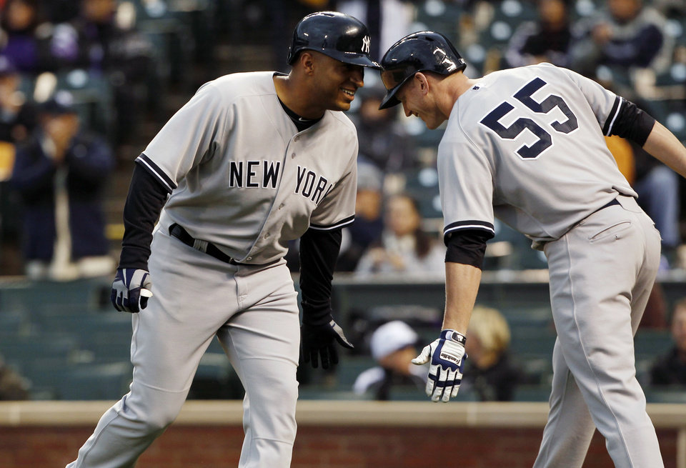 Photo - New York Yankees' Vernon Wells, left, is congratulated by teammate Lyle Overbay after hitting a two-run home run against the Colorado Rockies in the first inning of a baseball game in Denver on Wednesday, May 8, 2013. (AP Photo/David Zalubowski)